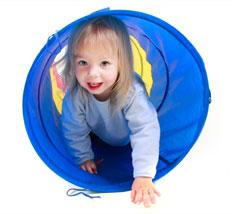 Kind krabbelt durch Tunnel